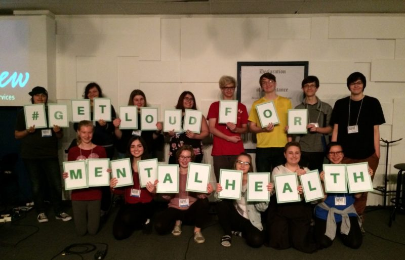 Group of youth holding up letters spelling get loud for mental health
