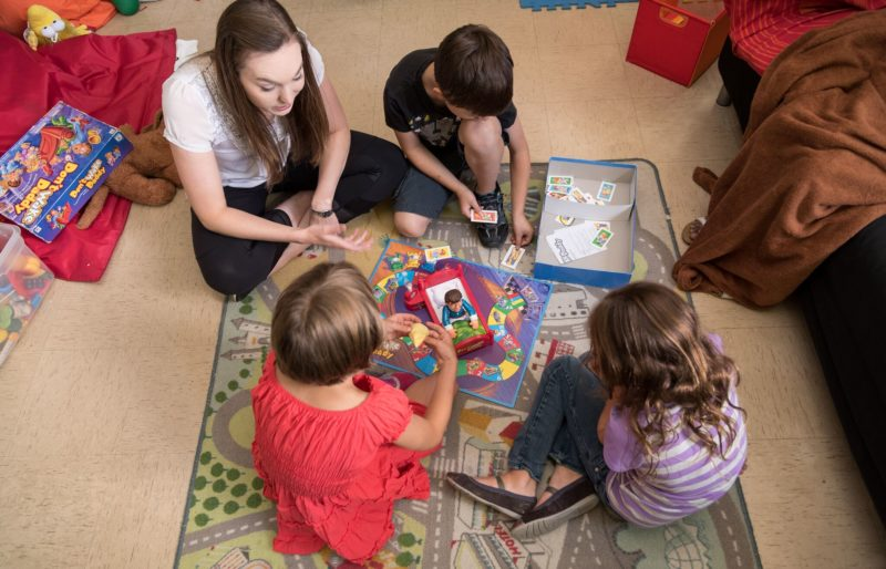Autism instructor and three children playing boardgame on the floor