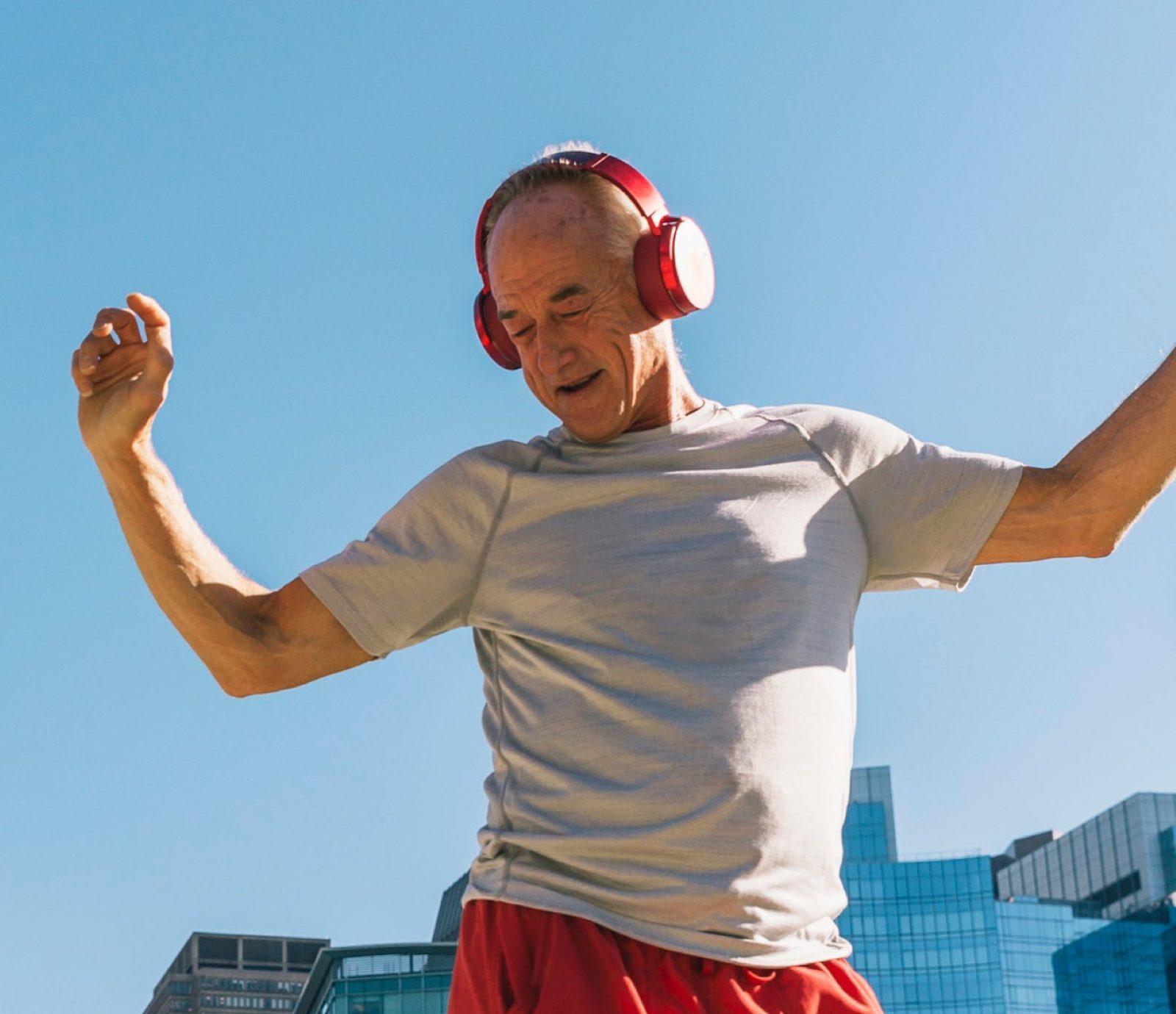 Older man jumping against a blue sky