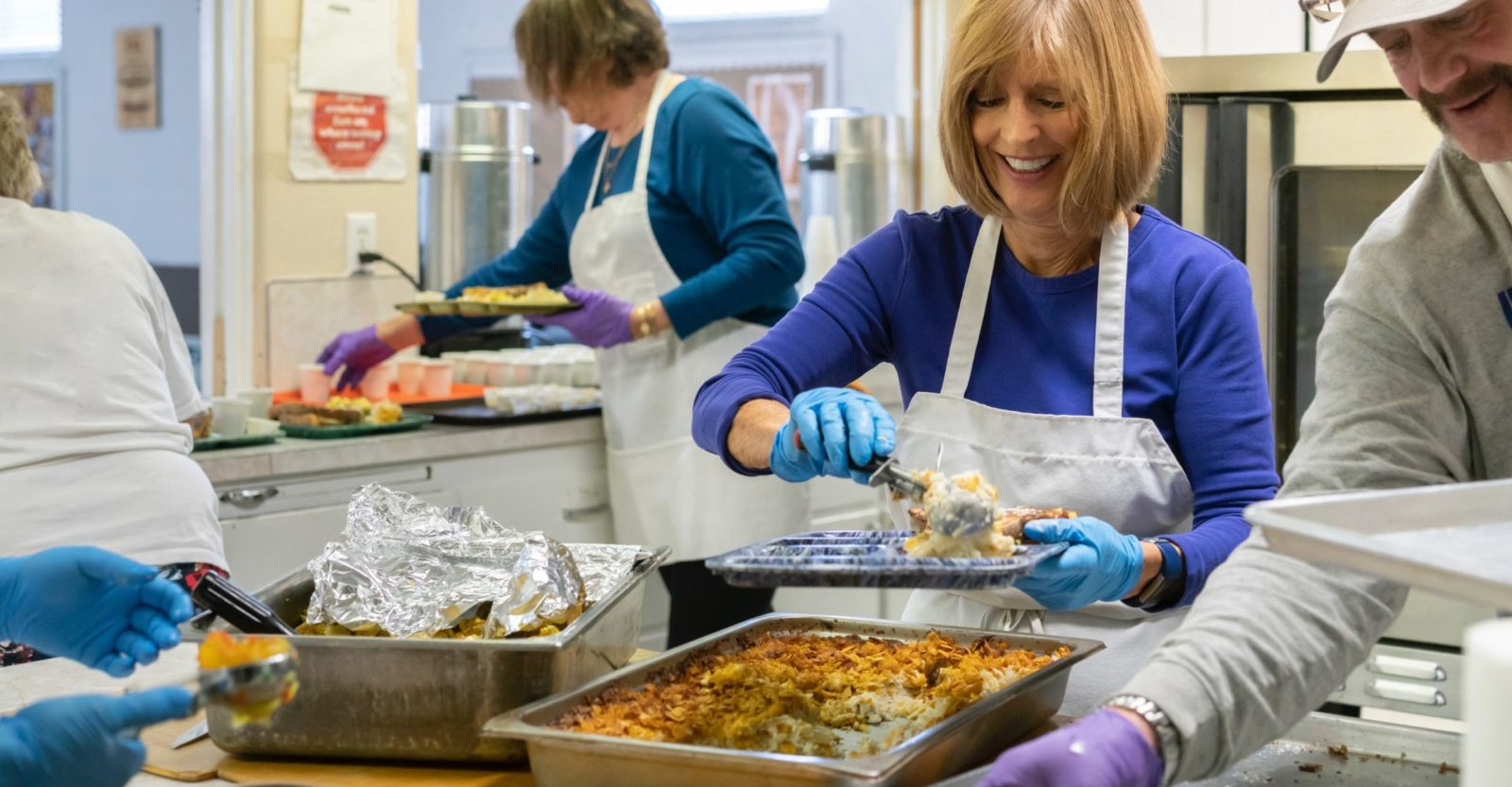 Woman volunteering at a community kitchen serving food