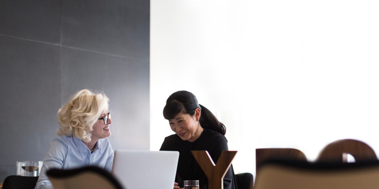 Cheerful businesswoman with smiling partner working on laptop and discussing ideas
