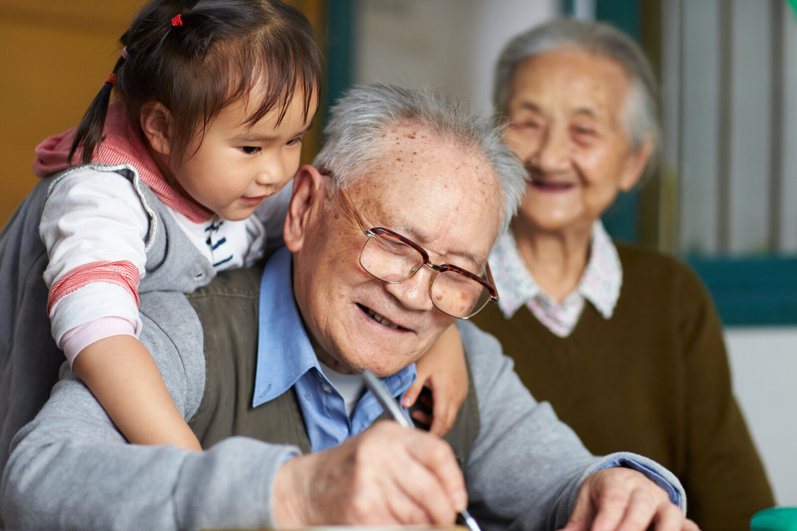 Young girl and great grandfather writing together