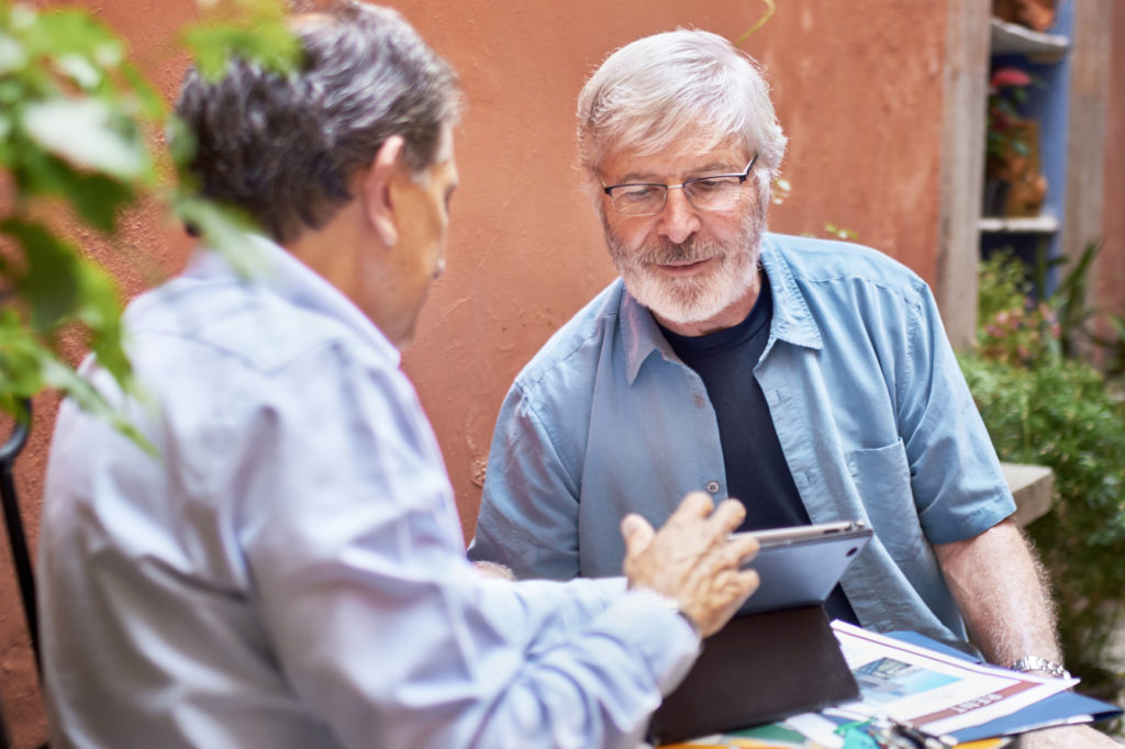 Two men discussing a plan on a tablet computer outdoors