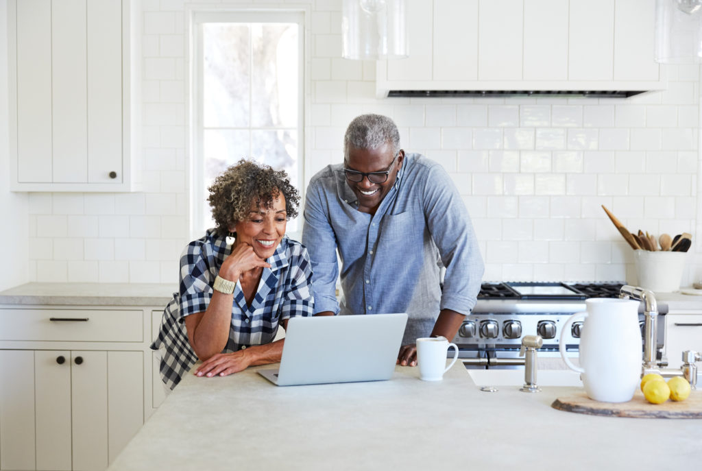 Senior couple on computer in the kitchen together