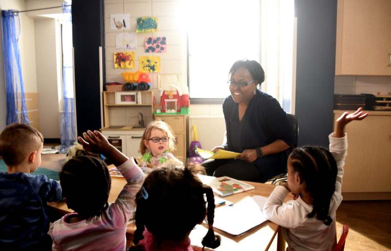 Woman teaching in front of three children