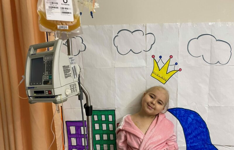 Young patient with cancer smiles while standing next to a bag of donated blood platelets in a hospital