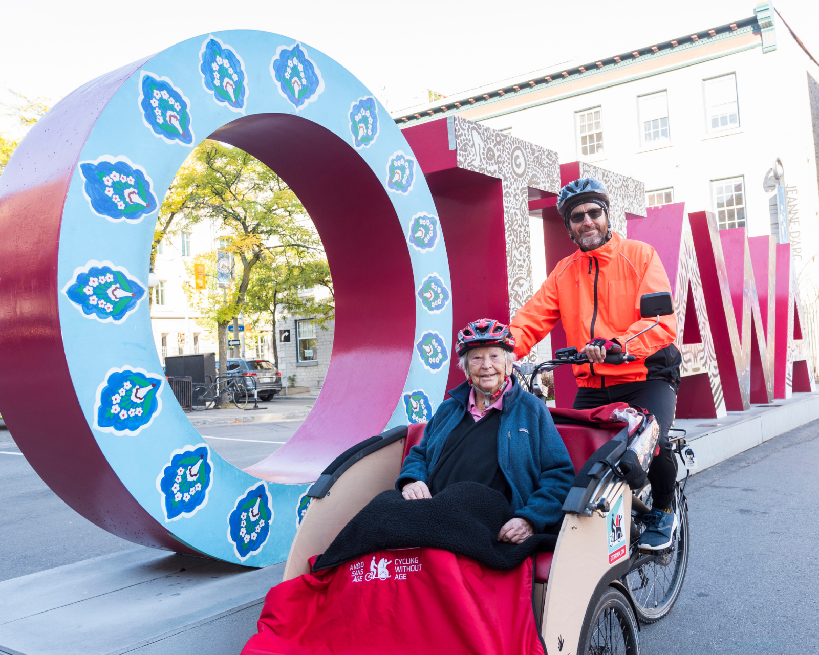 Bruyère patient with staff member on Cycling Without Age bike in front of Ottawa Sign