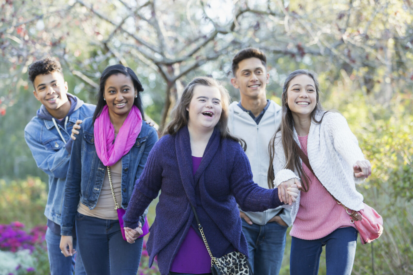 A group of multi-ethnic teenagers walking in a park. The girl in the purple sweater has Down's syndrome.