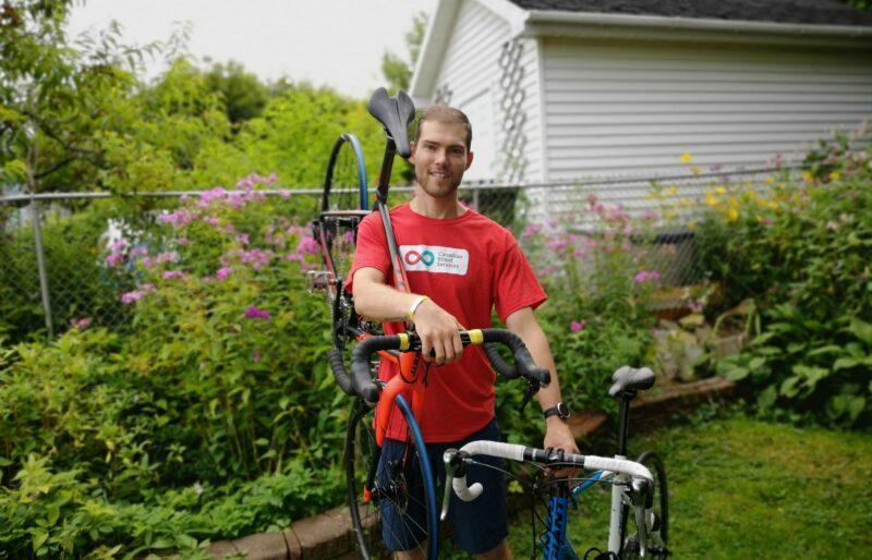 Young man stands smiling in a garden with a bike on his shoulder
