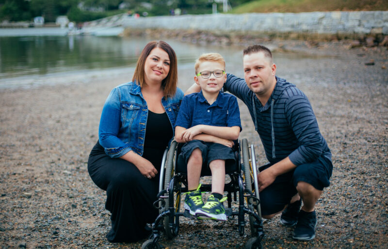 Owen is in wheelchair with his parents kneeling on both sides of him on a pebbled beach