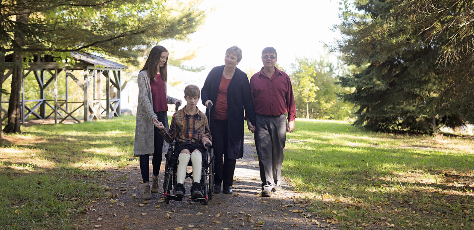 Patrick is in his wheelchair in a forest surrounded by his older parents and sister, holding his hand