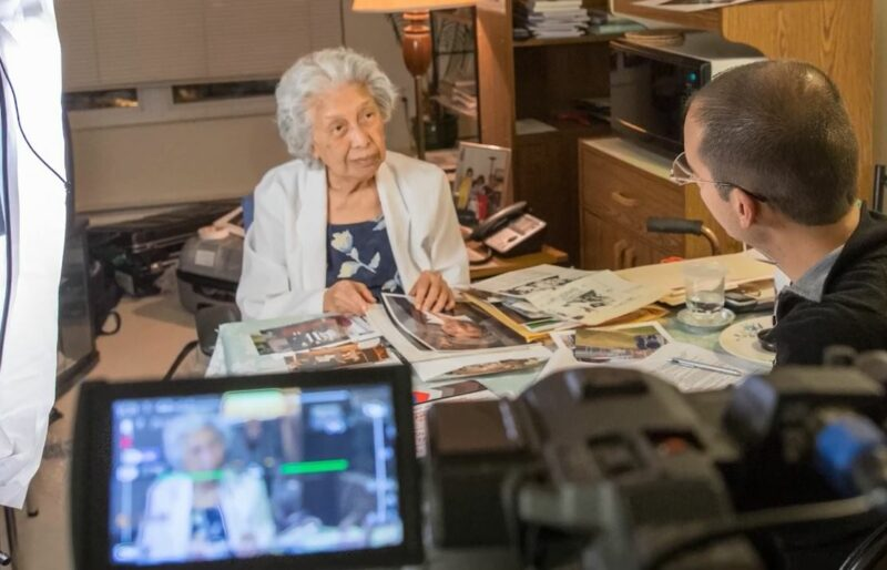 A woman stands at a desk with photos gathered in front of her as she speaks to an Oral Historian from the Museum who is facing her. The conversation is being recorded with a video camera.