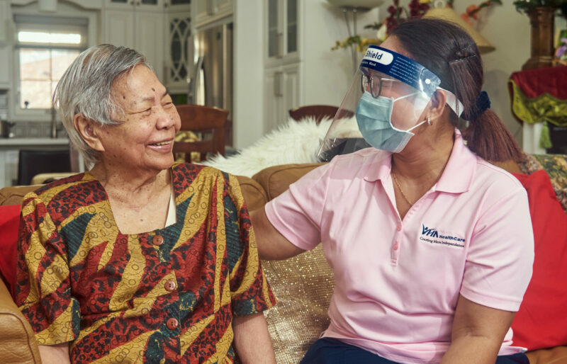 A woman wearing a face shield and a mask with her arm around an elderly Asian woman who is looking at her and smiling.