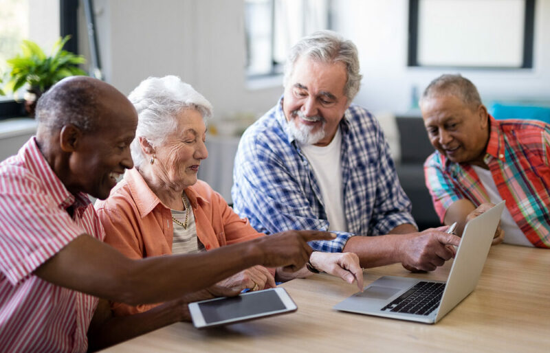 Happy group of senior men and woman using laptop