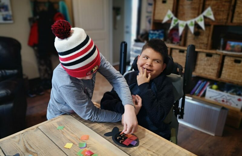 Boy with disability being assist by young boy