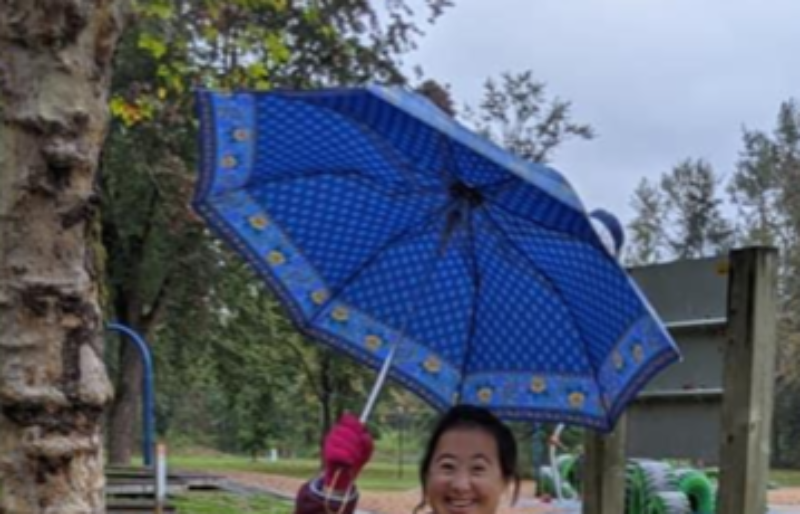 A women with Down syndrome standing under a blue umbrella in the rain