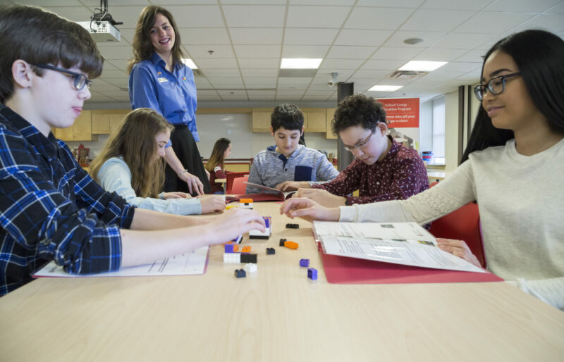 Students sit at a table in the Museum classroom facing each other as a Heritage Interpreter guides them through one of our education programs involving lego blocks.