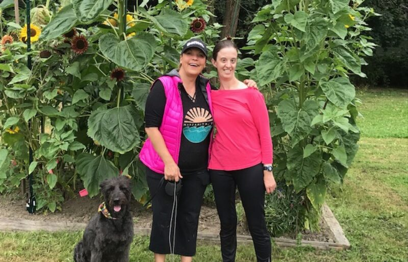 Two women with a black dog standing in front of giant sunflowers