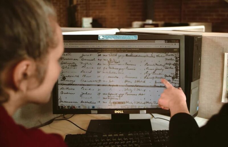 A woman faces a computer screen showing an immigration record of her family while one of our researchers points to a specific word on the screen during a genealogy family research.