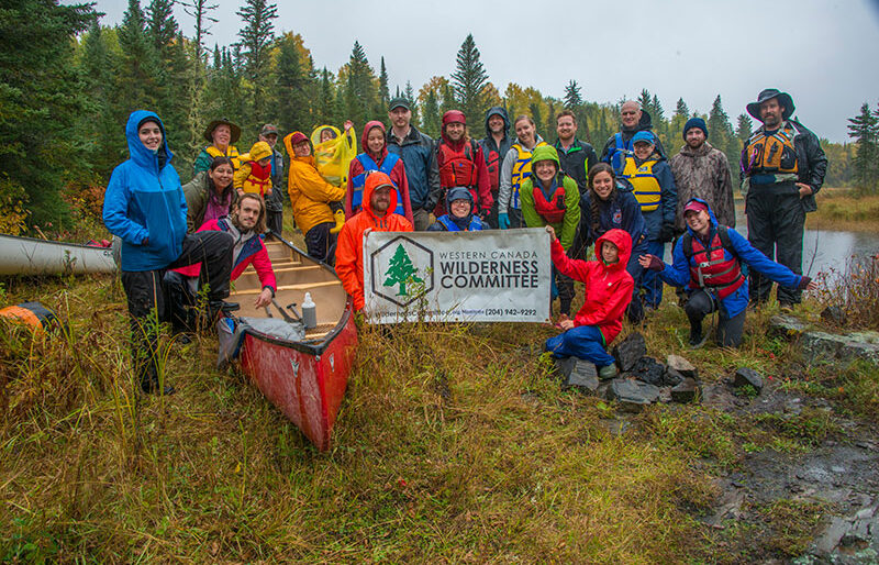 A group of people gather on a grassy slope in their raingear, canoe and Wilderness Committee sign in the fore.