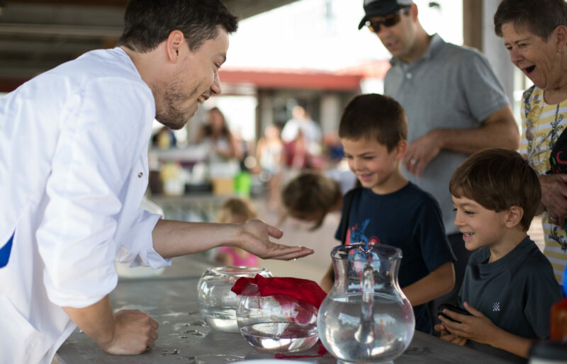 Volunteer showing science activity to students and adults