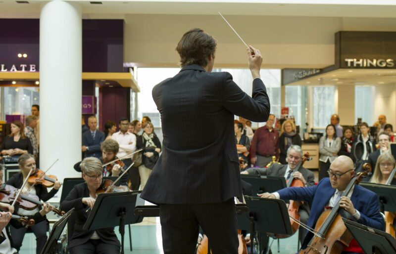 Associate conductor leads orchestra performance in lobby of public building