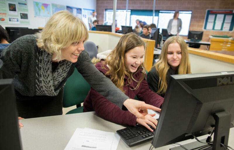 Educator pointing to a computer with students
