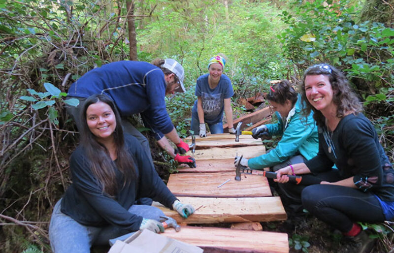 A few volunteers pose while nailing cedar planks into the boardwalk.