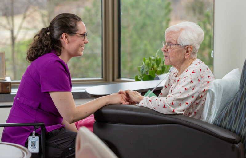 A care provider holds a patient's hands.