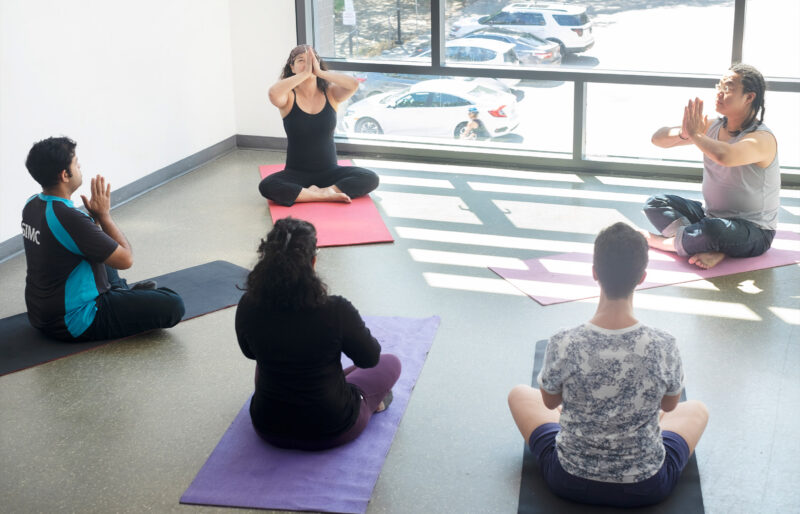 People sitting on yoga mats in a room.