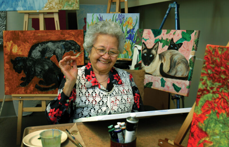 An elderly woman paints a picture
