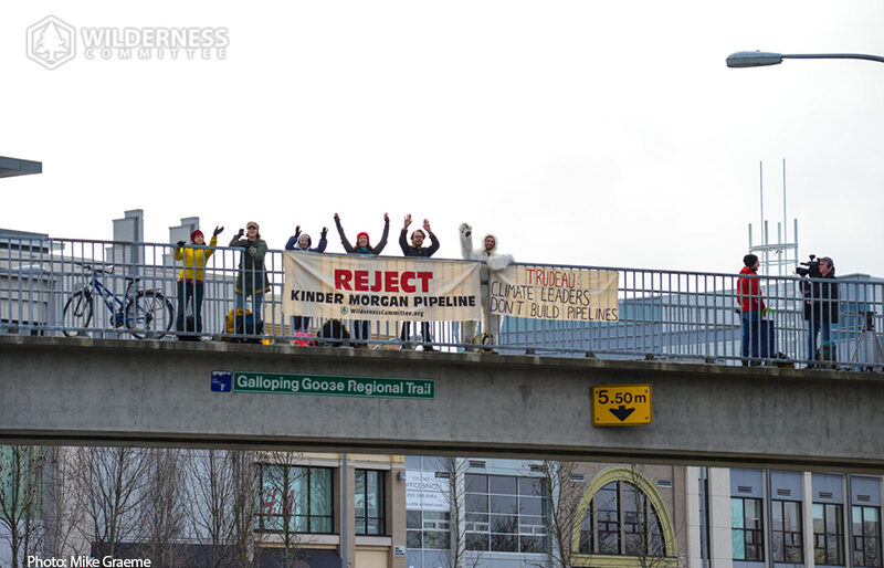 A group of people stand with a banner reading