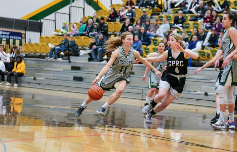 Women's basketball player dribbles around opposition.