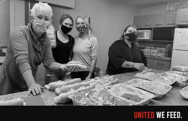 Four women wearing medical masks are making sub sandwiches in a kitchen