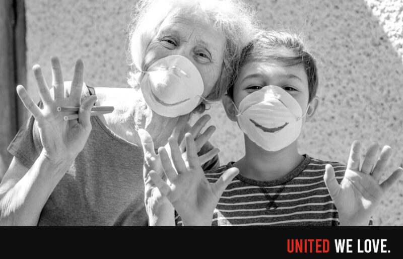 A lady with grey hair and a young child have drawn smiles on their medical masks