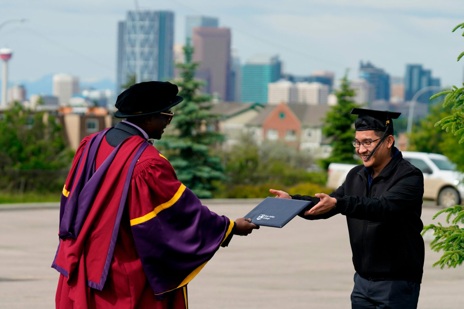 Dr. Misheck Mwaba, Bow Valley College's President & CEO, congratulates 2020 valedictorian Neil Tan at a physically distanced convocation visit.