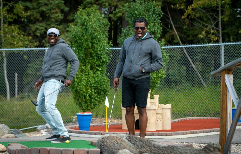 Two people celebrate a great putt at Little Al's Mini Golf at Waskesiu Lake