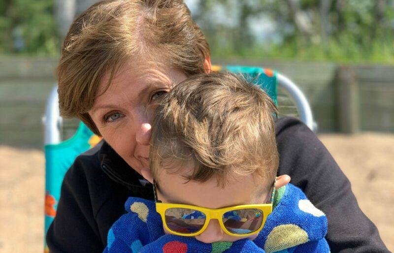 A grandma and grandson enjoy a snuggle on the beach at Waskesiu Lake