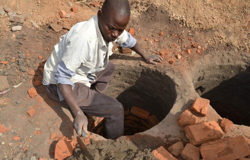 Lining a pit with handmade bricks