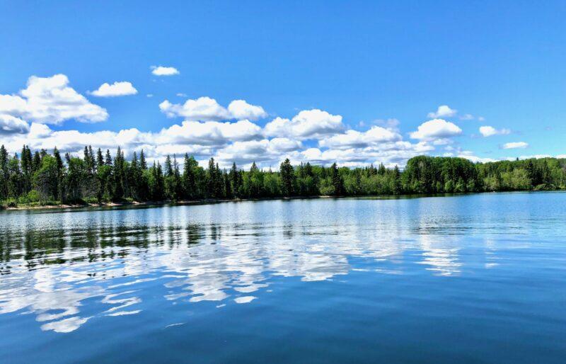 A beautiful photo of Waskesiu Lake reflected in the water