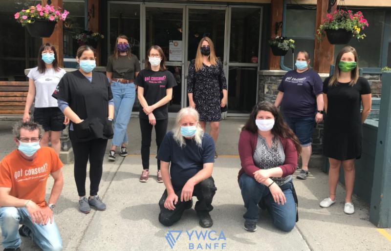 YWCA Banff staff posing in front of YWCA building wearing masks.