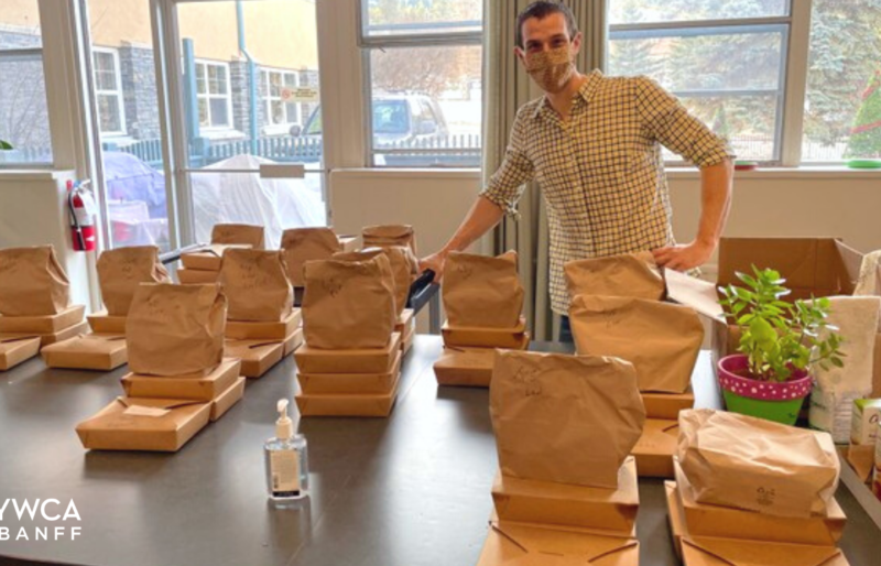A YWCA staff member stands behind a table with bags and boxes of food.