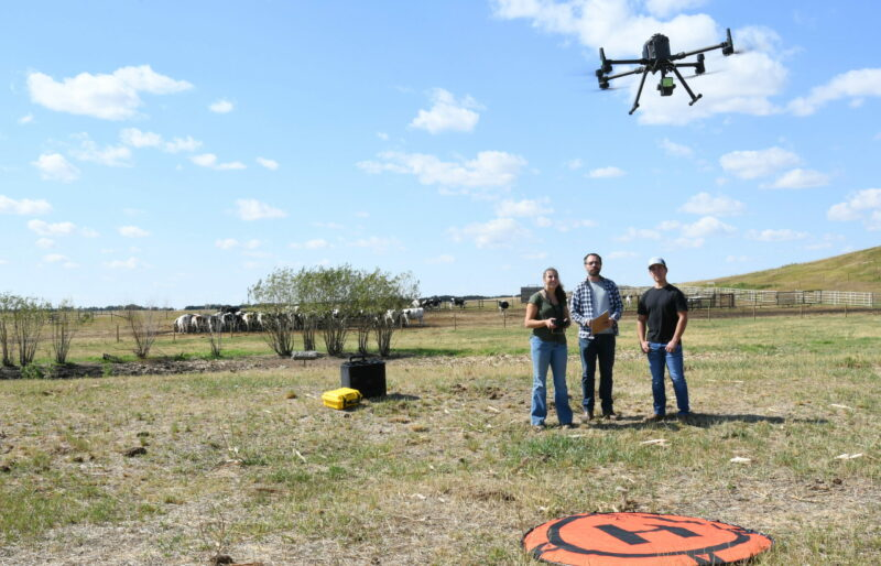 Student flying drone while instructor and another student watch