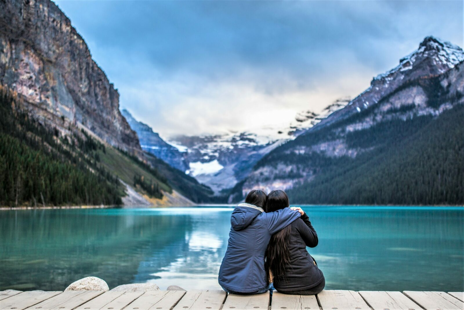 Image depicts two people sitting on a dock looking at Lake Louise. One person has their arm around the other's shoulder.